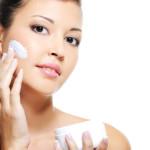 בחורה מורחת קרם הגנה על העור